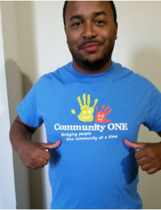 A Community ONE Volunteer sports his t-shirt at an event.